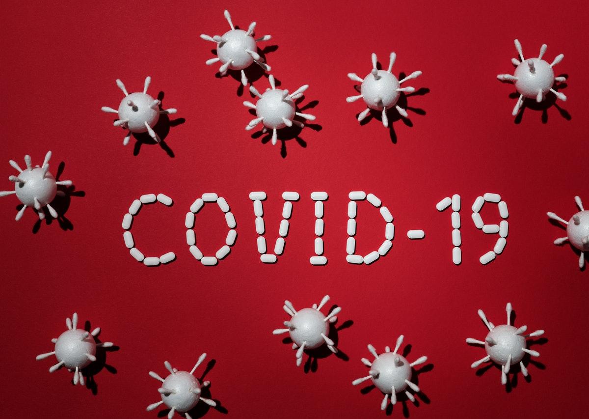 czerwona plansza z napisem covid-19 i bakteriami